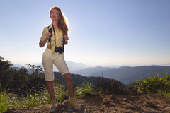 Woman traveler. Beautiful, young, red-haired girl tourist standing on top of a mountain with a camera stock photos