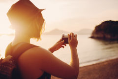 Woman traveler with camera taking photo near sea Stock Images