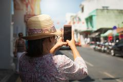 Woman traveler in casual dress taking picture in thalang road with blurred chino portuguese style building royalty free stock photo
