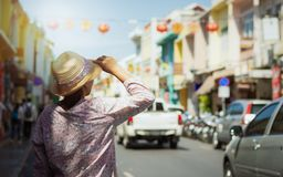 Woman traveler in casual dress walking in thalang road with blurred chino portuguese style building royalty free stock image