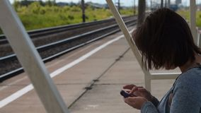 Woman traveler with cell waiting for train on platform. Woman commuter using smart phone when waiting for the train on platform in small town stock footage