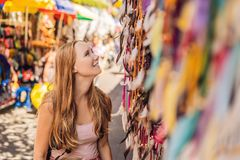 Woman traveler choose souvenirs in the market at Ubud in Bali, Indonesia royalty free stock photos