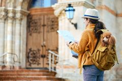 Woman traveler with dog in the backpack examines architectural monument . royalty free stock image