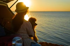 Woman traveler with dog sitting in car trunk near sea, watching sunset. royalty free stock photography