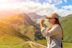 Woman drinking water in summer sunlight Stock Images