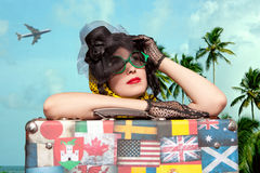 Woman traveler embraces a vintage suitcase. Photo in old image s Stock Image