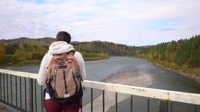 The woman the traveler goes along the bridge through the mountain river. Fall. stock video