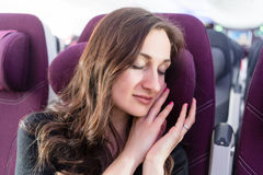 Woman traveler having nap in airplane cabin travelling to vacation stock photography
