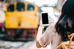 Woman traveler holding blank screen mobile smartphone royalty free stock images