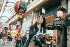 Woman traveler holding guidebook travel in japan. Cheerful woman traveler with camera holding a guidebook travel in japan. osaka travel concept. Happy tourist royalty free stock photo