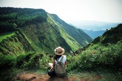Woman traveler in Azores. Woman traveler holding hat and looking at amazing mountains and forest, wanderlust travel concept, space for text, atmospheric epic royalty free stock images