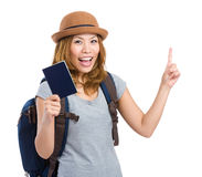 Woman traveler holding passport and finger pointing up Stock Photos