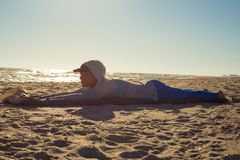 Woman traveler lays on the beach. Relaxing and enjoying life on a quiet evening, against the sparkling sea. Magic vacation on the shore of the wild sea. Back stock photo