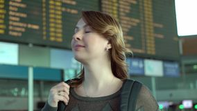 Woman looking at information board in airport. Woman traveler looking at information board in airport stock video