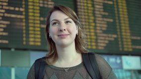 Woman looking at information board in airport. Woman traveler looking at information board in airport stock footage