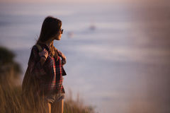 Woman traveler looks at the edge of the cliff on the sea bay of mountains in the background at sunset Royalty Free Stock Images