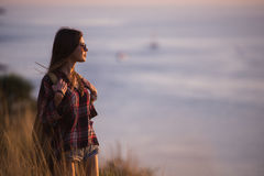 Woman traveler looks at the edge of the cliff on the sea bay of mountains in the background at sunset Royalty Free Stock Image
