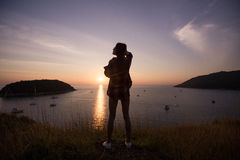Woman traveler looks at the edge of the cliff on the sea bay of mountains in the background at sunset Stock Image