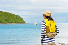 Woman traveler looks at the sea. In the morning Stock Photos