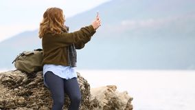A woman traveler makes a panorama. A woman traveler with a backpack stands on a rock on the sea shore against the backdrop of the mountains and makes a panorama stock video
