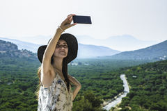 Woman traveler makes a self in the background beautiful natural view mountain on the island of Crete. Concept - tourism, travel, p Royalty Free Stock Images