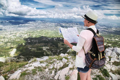 Woman traveler with map on high mountains Stock Photography