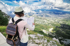 Woman traveler with map on high mountains Stock Photos