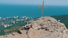 Woman traveler meditates in mountains, sitting on top of a cliff in the lotus position stock video