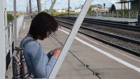 Woman traveler with mobile waiting for train on platform. Woman commuter using mobile phone when waiting for the train on platform in small town stock video footage