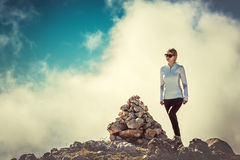Woman Traveler on Mountain Summit with stones. Way sign and Clouds Sky on background Hiking Mountaineering Lifestyle summer Stock Image