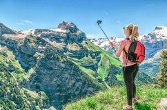 Woman traveler photographing herself, making a salfi on the smar. Tphone, against the backdrop of the mountain peaks of Switzerland Royalty Free Stock Photos