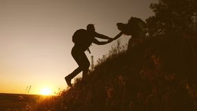 A woman traveler reaches out to a man climbing a hilltop in the sunset light. travelers climb the cliff holding hands stock footage