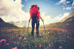 Woman Traveler with red backpack hiking Travel Lifestyle. Concept Summer vacations outdoor mountains and flowers valley on background Royalty Free Stock Photography
