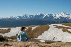 Woman traveler is relaxing admiring mountain range Royalty Free Stock Photos