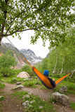 Woman traveler relaxing in hammock, next to glacier Stock Photo