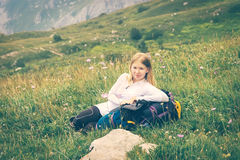 Woman traveler relaxing outdoor on green valley with backpack Royalty Free Stock Image