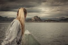 Woman traveler sailing on boat towards shore with with Mountains landscape on horizon in overcast day with dramatic sky Stock Photo