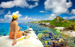 Woman traveler sails on a boat enjoying the coral reef around is Royalty Free Stock Photos