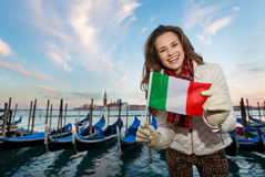 Woman traveler showing Italian flag on embankment in Venice Stock Image