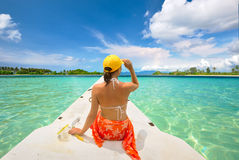 Woman traveler sit on boat at sunny day and looking to a clean s Royalty Free Stock Images