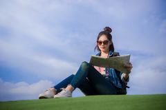 Woman traveler sit down on green grass and looking a map on the Royalty Free Stock Photos