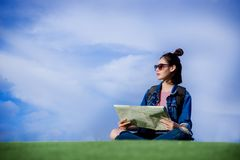 Woman traveler sit down on green grass and looking a map on the Royalty Free Stock Image