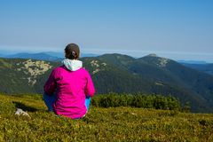 Woman traveler sits on green mountain meadow. And admiring amazing view of green hills which stretching to the horizon in blue haze. Back view Royalty Free Stock Image