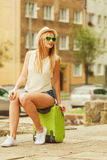 Woman traveler sits on suitcase waiting for car. Hitch hiking and travelling. Lovely smiling cute girl sits on green suitcase luggage baggage waiting for car Royalty Free Stock Photo
