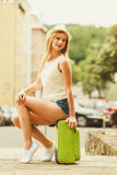 Woman traveler sits on suitcase waiting for car. Hitch hiking and travelling. Lovely smiling cute girl sits on green suitcase luggage baggage waiting for car Royalty Free Stock Photos