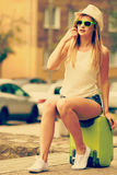 Woman traveler sits on suitcase waiting for car. Royalty Free Stock Image