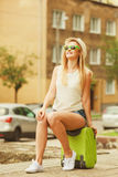 Woman traveler sits on suitcase waiting for car. Stock Photo