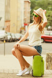 Woman traveler sits on suitcase waiting for car. Royalty Free Stock Photo