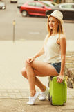 Woman traveler sits on suitcase waiting for car. Stock Photography