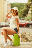 Woman traveler sits on suitcase waiting for car. Royalty Free Stock Photos